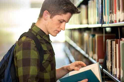 Male student looking at books in the library