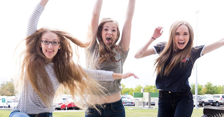 three female students jumping up into the air celebrating